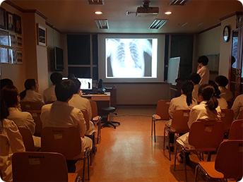 프로젝트 빔을 이용해 x-ray 사진을 보고 있는 컨퍼런스 장면
